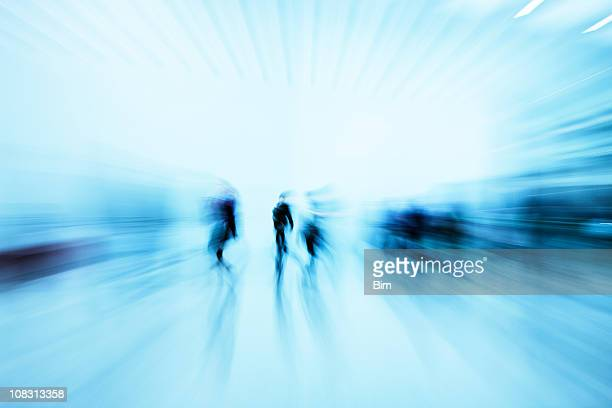 Silhouettes of Pedestrians Rushing in Blue Corridor, Blurred Motion