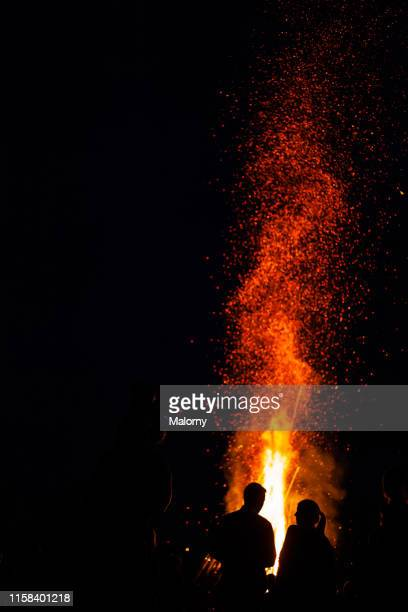 silhouettes of people against summer bonfire. midsummer festival. solstice celebrations. - flame stock pictures, royalty-free photos & images
