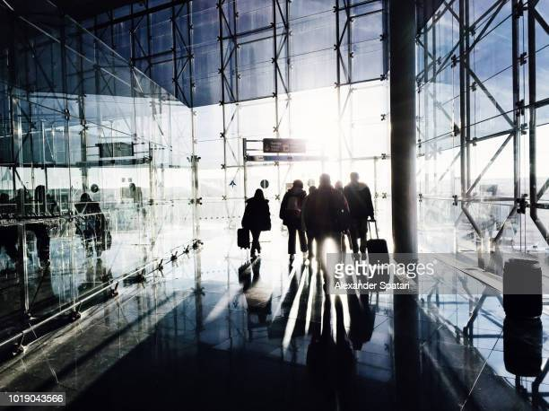 Silhouettes of people arriving at the airport terminal and walking through the glass door