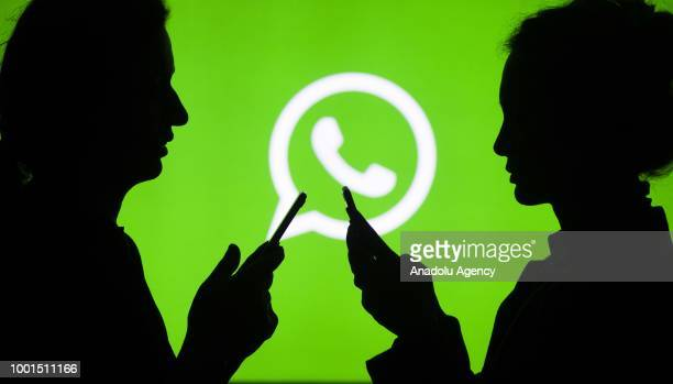 Silhouettes of people holding mobile phones are seen in front of the logo of WhatsApp application in Ankara Turkey on July 18 2018