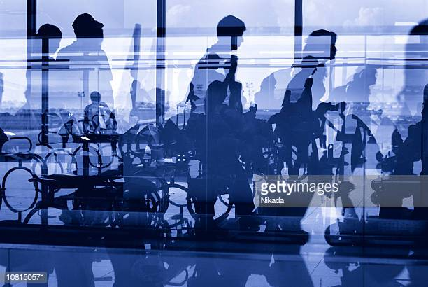 Silhouettes of People in Airport Window