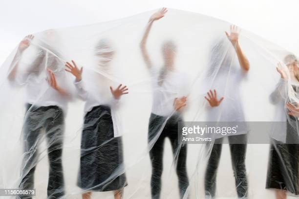 silhouettes of people in black and white clothes behind a translucent veil - white shirt stock pictures, royalty-free photos & images
