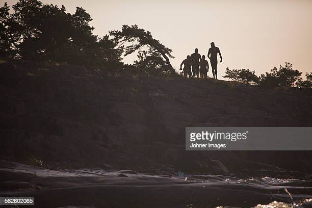 Silhouettes of people on cliff