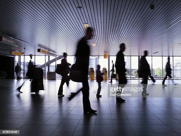 silhouettes of people passing at busy airport - netherlands stock pictures, royalty-free photos & images