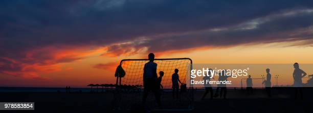 silhouettes of people playing soccer on beach at sunset - deporte de equipo fotografías e imágenes de stock