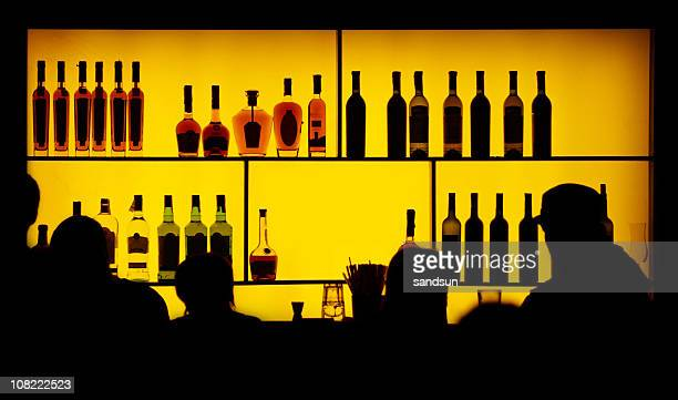 Silhouettes of people standing next to a bar counter