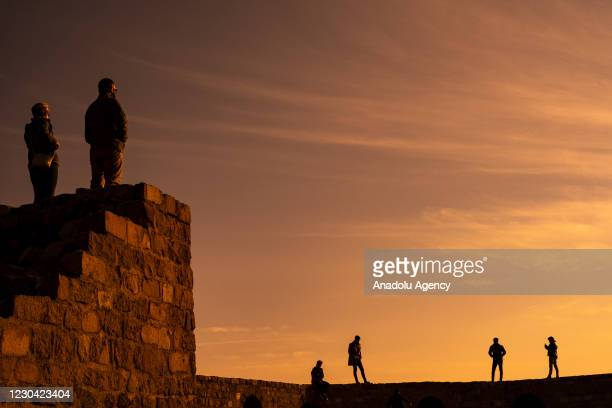 Silhouettes of people touring the Ankara Castle during sunset after a nationwide curfew spanning the traditional New Year's holiday started Thursday...