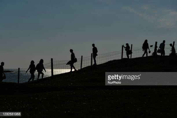 Silhouettes of people walking and returning to Dogs Bay beach, in Ervallagh, during the COVID-19 lockdown. Next Monday there will be another slight...