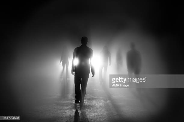 silhouettes of people walking into light - raadsel stockfoto's en -beelden