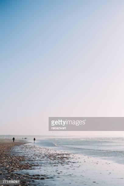 Silhouettes of people walking on beach, IJmuiden, Holland