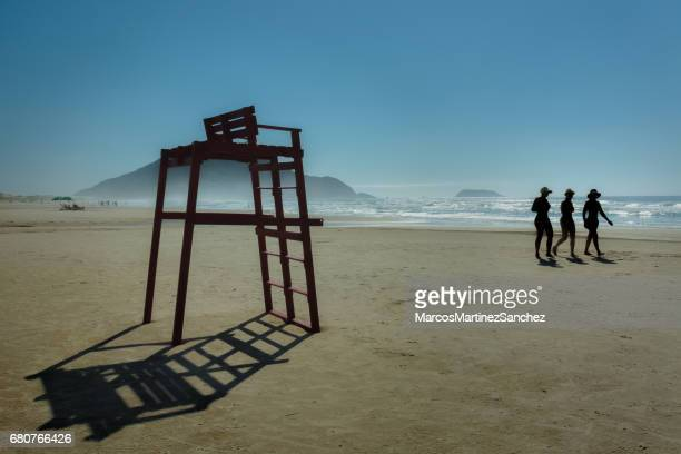 Silhouettes of people walking with a lifeguard chair in Santinho Beach, Santa Catarina, Brazil