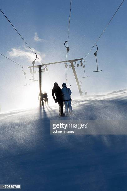 Silhouettes of people with ski lift in background
