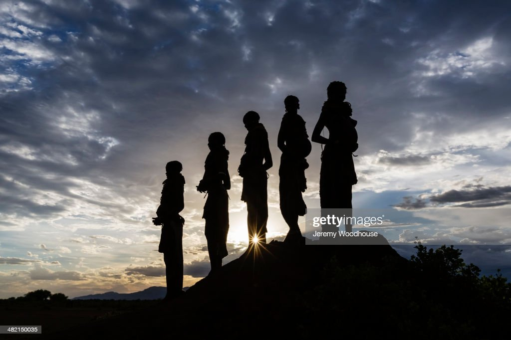 Silhouettes of pregnant woman under cloudy sky at sunset, Nyangaton, Ethiopia : Stock Photo