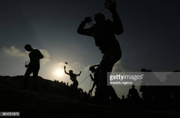 Silhouettes of protesters throwing rocks in response to Israeli soldiers' intervention in a demonstration against US decision to recognize Jerusalem...
