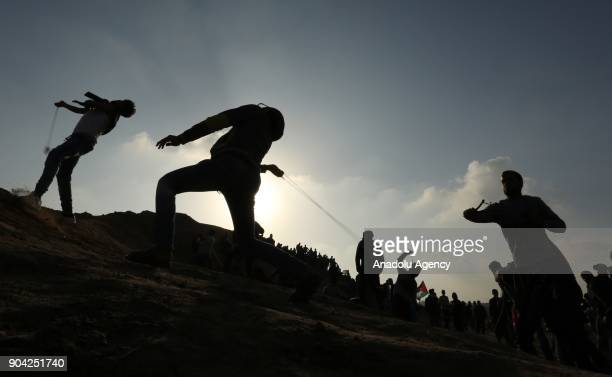 Silhouettes of protesters throwing rocks with slingshots in response to Israeli soldiers' intervention in a demonstration against US decision to...