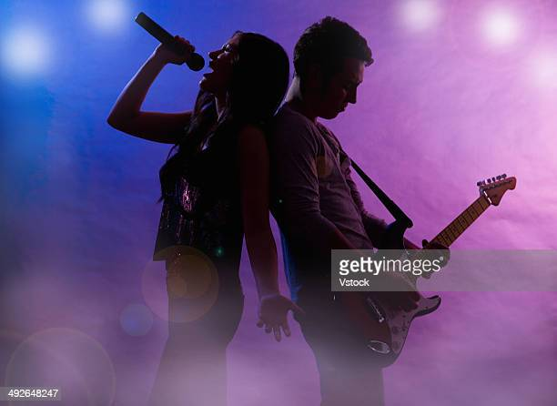 silhouettes of singer and guitar player on stage - duet stock pictures, royalty-free photos & images