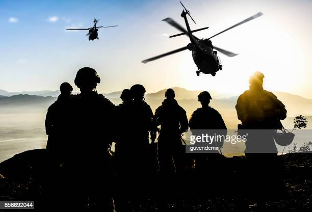 silhouettes of soldiers during military mission at dusk - army soldier stock photos and pictures