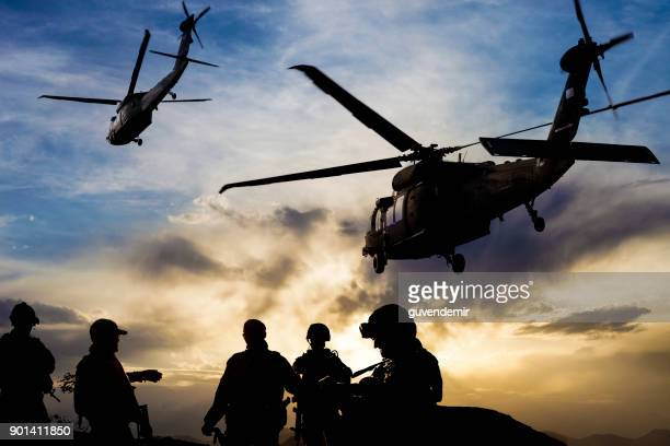 silhouettes of soldiers during military mission at dusk - helicopter stock pictures, royalty-free photos & images