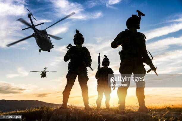 silhouettes of soldiers during military mission at sunset - army soldier stock pictures, royalty-free photos & images
