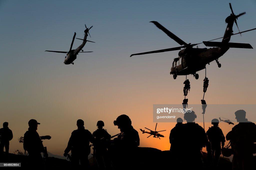 Siluetas de soldados en misión militar al atardecer : Foto de stock
