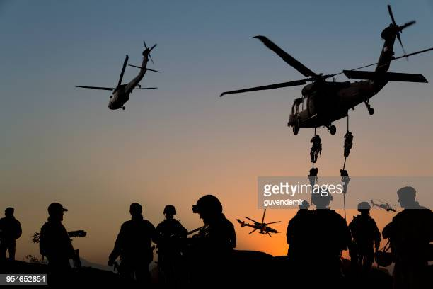 silhouettes of soldiers on military mission at dusk - personale militare foto e immagini stock