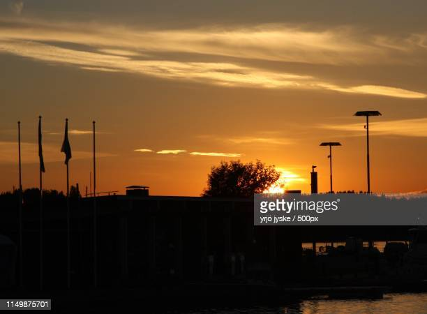 silhouettes of street lights and flagpoles against sky at sunset - flagpole sitting stock photos and pictures