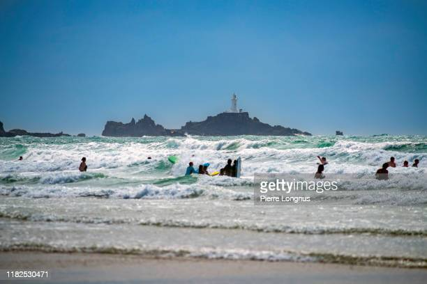 silhouettes of surfers and swimmers, st. ouen's bay beach, pointe de la corbière lighthouse in backdrop - {{ contactusnotification.cta }} stock pictures, royalty-free photos & images