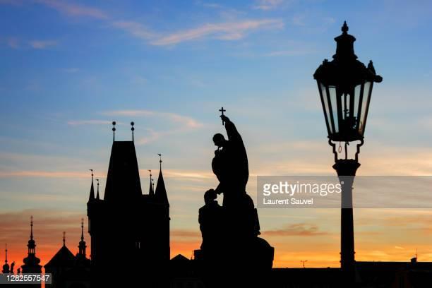 silhouettes of the statues on charles bridge and old town bridge tower at dawn, prague, czech republic - laurent sauvel photos et images de collection