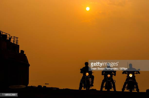 silhouettes of three bikers at sunrise, mumbai, maharashtra, india - contraluz - fotografias e filmes do acervo