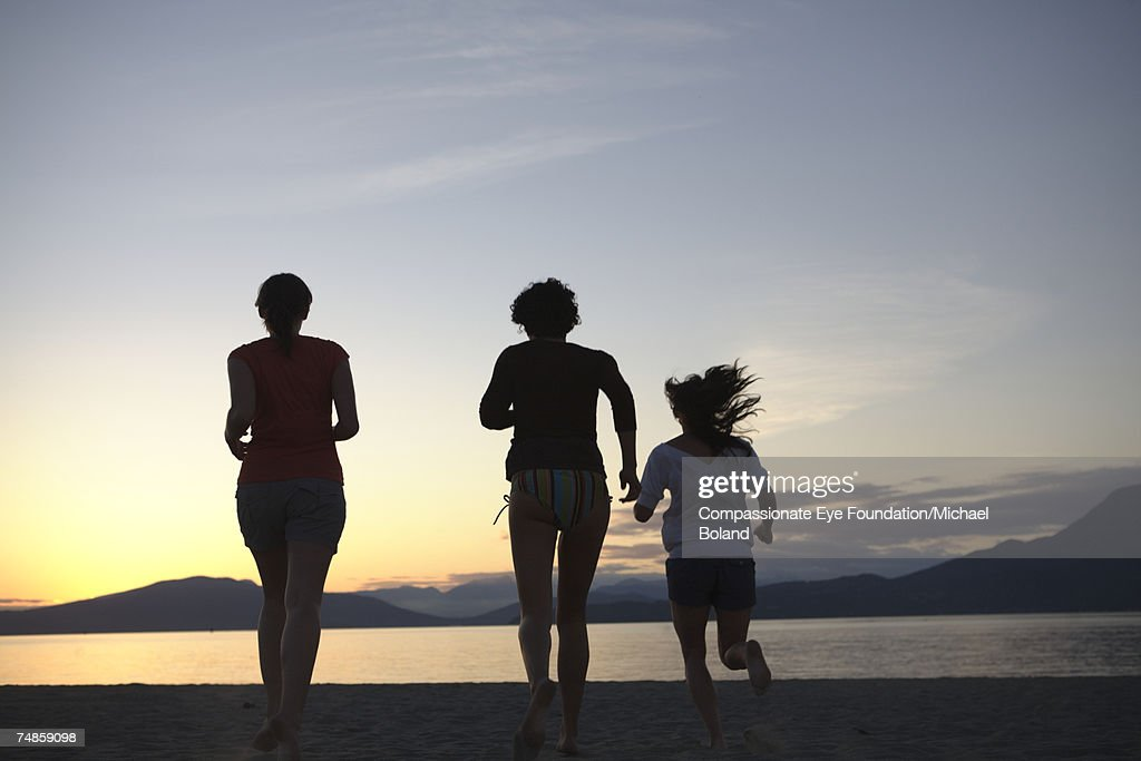 Silhouettes of three woman running toward ocean, dusk : Stock Photo