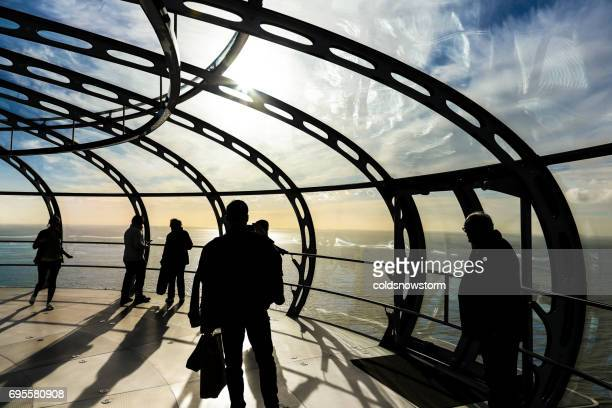 Silhouettes of tourists and people inside viewing tower, Brighton, UK