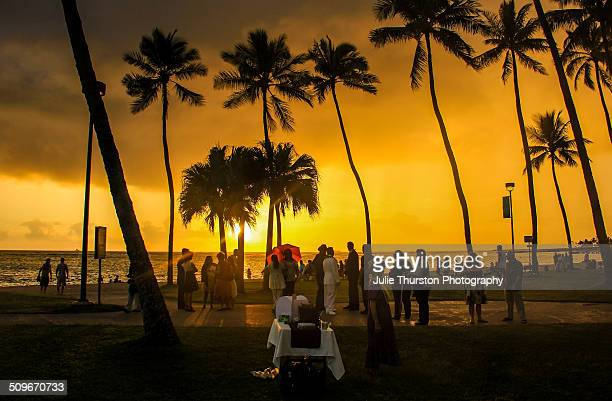 Silhouettes of Tropical Palm Trees and PeopleGuests Waiting For a Wedding to Begin Along Waikiki Beach a Tourist Vacation Travel Destination During a...