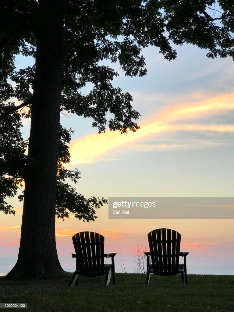 Silhouettes Of Two Adirondack Chairs Under A Tree At Sunset ...
