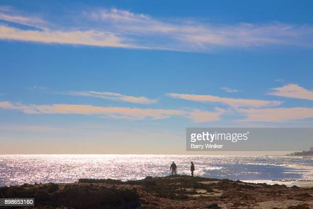 silhouettes of two adults on limestone shoreline, jupiter island - jupiter island stock photos and pictures