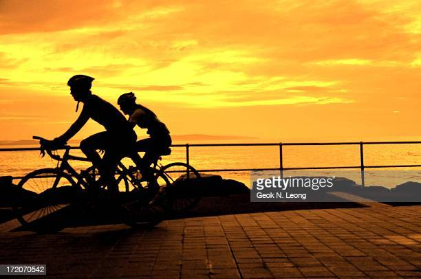 Silhouettes of two cyclists with helmets riding their bicycles at sunrise on Cronulla Beach, Sydney.