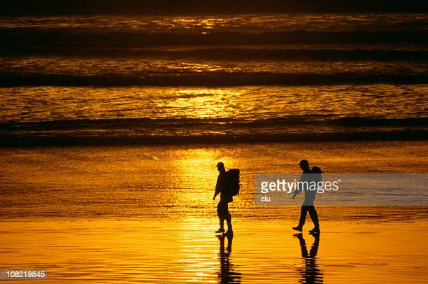 Silhouettes of Two Hikers Walking Along Beach at Sunset