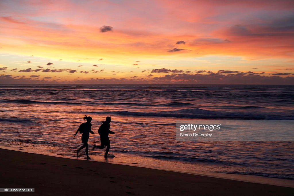 Silhouettes of two joggers on beach at sunset : Foto stock