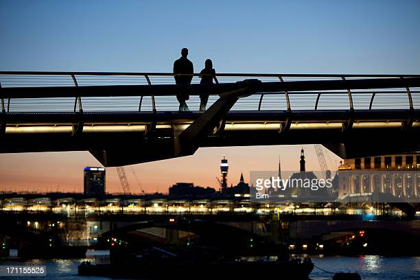 Silhouettes of Two Lovers on Millennium Bridge at Twilight, London