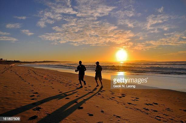 CONTENT] Silhouettes of two men jogging on Cronulla Beach at sunrise The morning sun casting long shadows on the beach and reflections on the water...