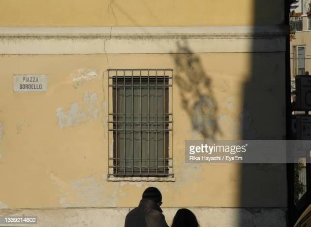 silhouettes of two people standing by window on building wall with a window and a shadow - mantua stock pictures, royalty-free photos & images