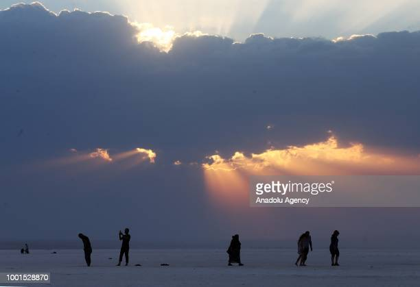 Silhouettes of visitors are seen as they walk on the dried ground of Lake Salt which is the second largest lake in Ankara Turkey on July 18 2018 Lake...