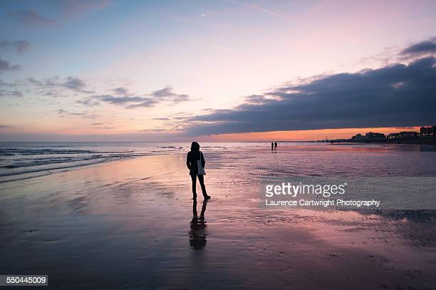 silhouettes of walkers on the beach at sunset - retreating ストックフォトと画像