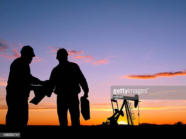 Silhouettes of workers and oil pump during sunset