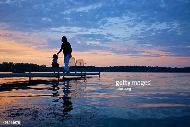 Silhouettes on a dock at during a sunset on a lake
