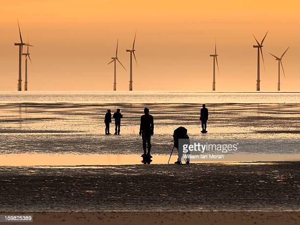 CONTENT] Silhouettes on Crosby beach Artist Anthony Gormleys Another place ironmen with photographer and other figures in front of some of the 90MW...