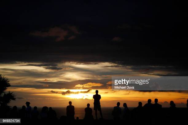 silhouettes people watching sunset dramatic clouds