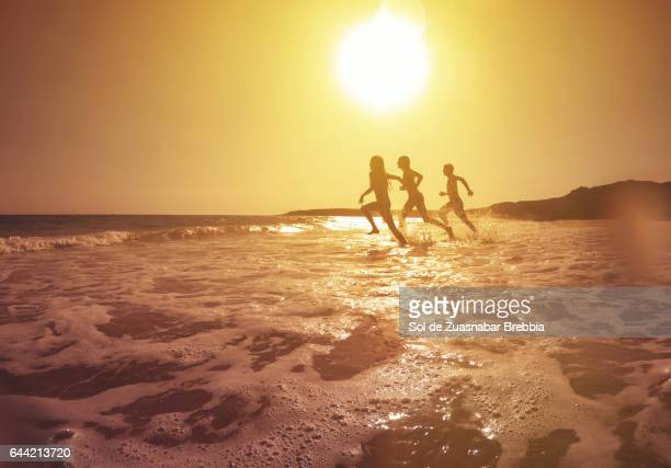 Silhouettes running towards the sea on a magical sunset