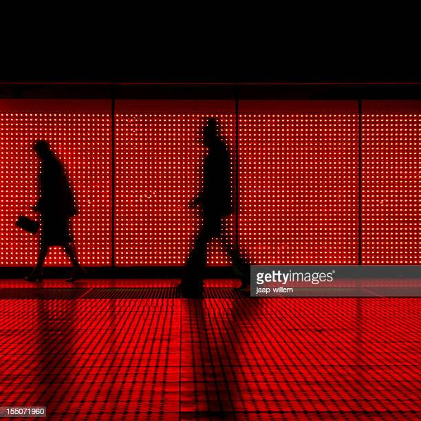 silhouettes walking on a moving sidewalk in red & black - global entry stock pictures, royalty-free photos & images