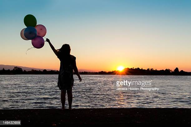 silhoutte of girl with balloons - マウンテンビュー ストックフォトと画像