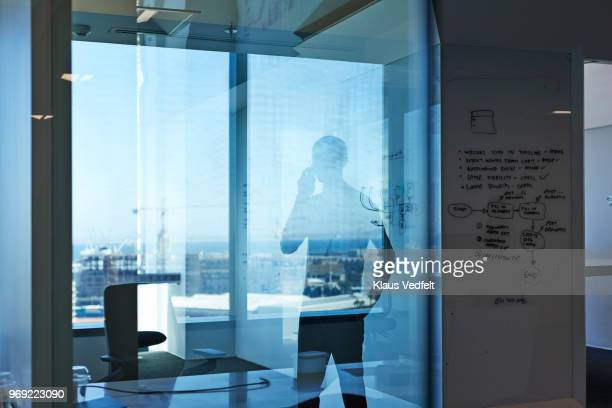 silhuet of businessman talking on the phone in office - premium access stock pictures, royalty-free photos & images
